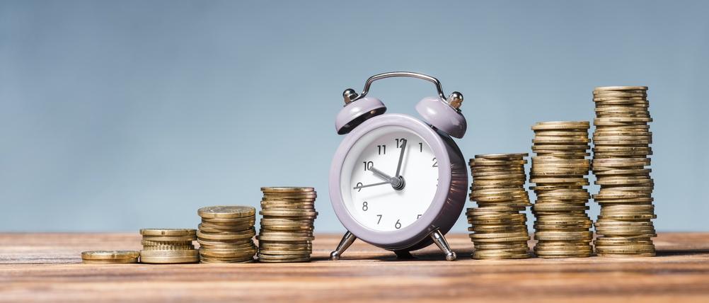 Sie sehen eine Uhr und stetig steigende Stapel von Geldmünzen